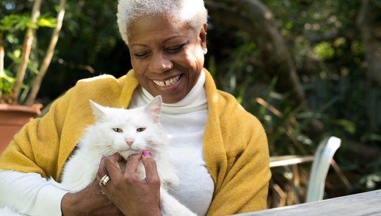 Una mujer mayor se sienta en el jardín abrazando a un hermoso gato blanco.